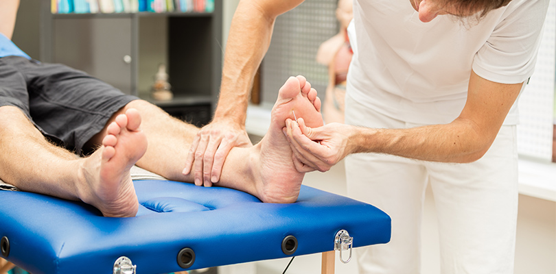 Man giving another man acupuncture on bottom of feet